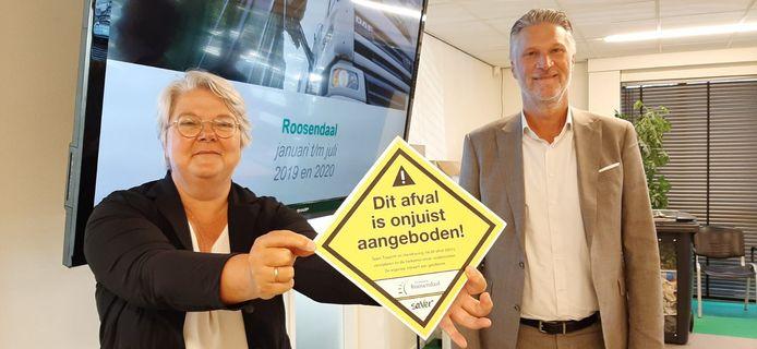 Wethouder Klaar Koenraad van de gemeente Roosendaal toont de sticker die op illegaal gedumpte afvalzakken wordt geplakt. Rechts directeur Pascal de Klerk van Saver.