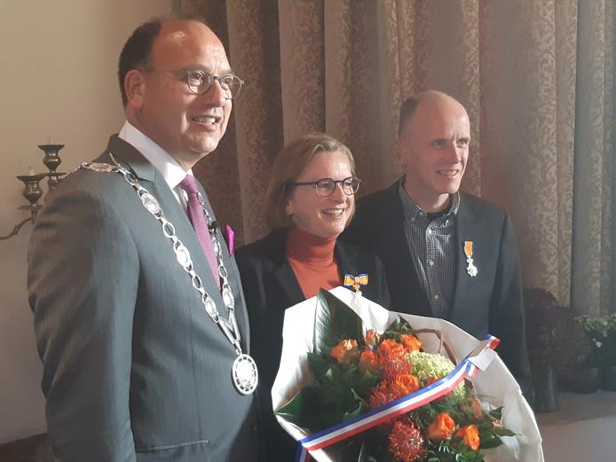 Burgemeester De Baat reikt de lintjes uit aan Sylvia en Carlo Jansen.