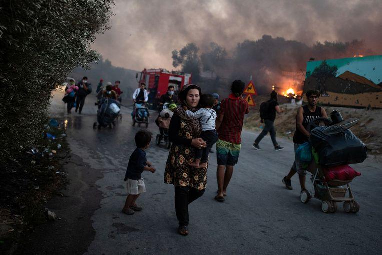 Een vrouw draagt haar baby tijdens de vlucht weg van de brand.  Beeld REUTERS