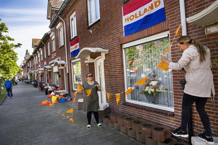 Natasja Schiermanni (links) en Chantal Plasman hangen oranje versiering op in de Ahornstraat in Breda. Beeld Arie Kievit