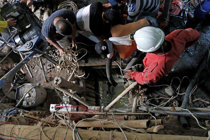 Reddingswerkers proberen de vermiste mijnwerkers te bevrijden.