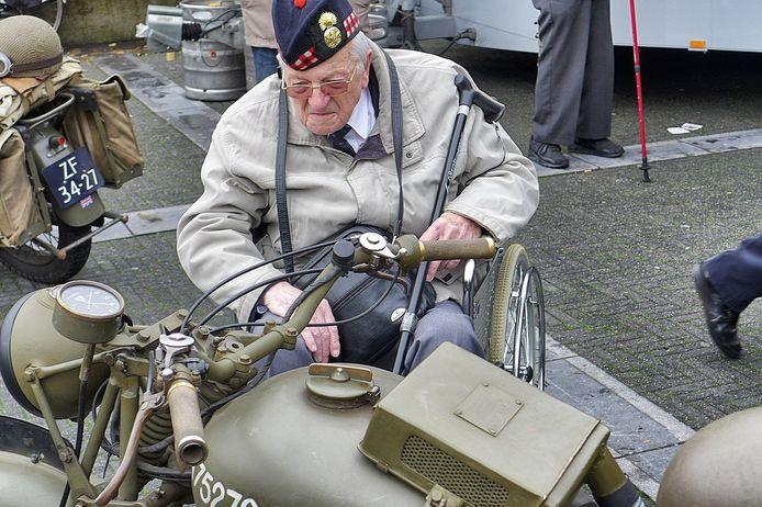 Een veteraan bekijkt een antieke legermotorfiets op het Willemsplein in Tilburg