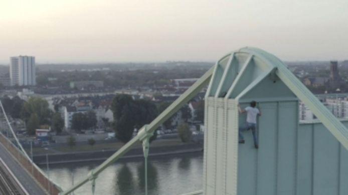 Un casse-cou grimpe au sommet d'un pont pour sauter en parachute.
