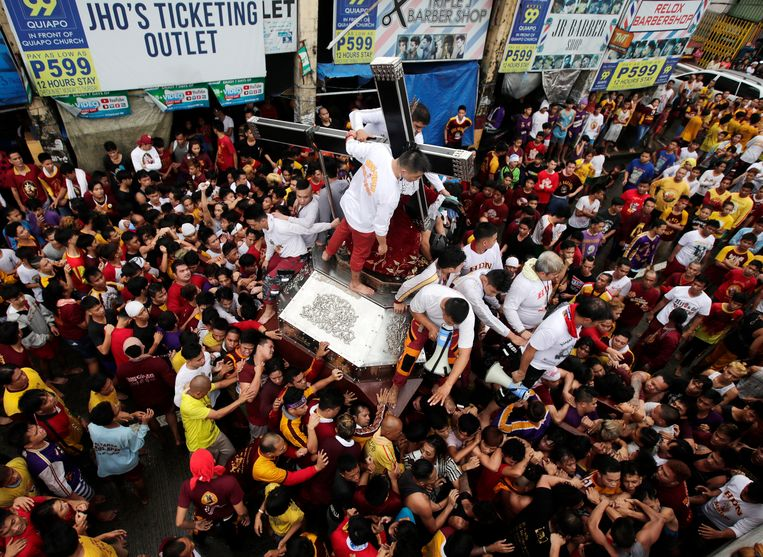 Duizenden Filipijnse katholieken op blote voeten omringen tijdens een nieuwjaarsprocessie in Manilla het beeld van de Zwarte Jezus uit Nazareth.  Beeld EPA
