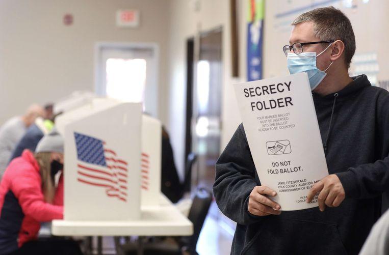 Een man met een stembiljet in een stembureau in Des Moines, Iowa. Beeld AFP