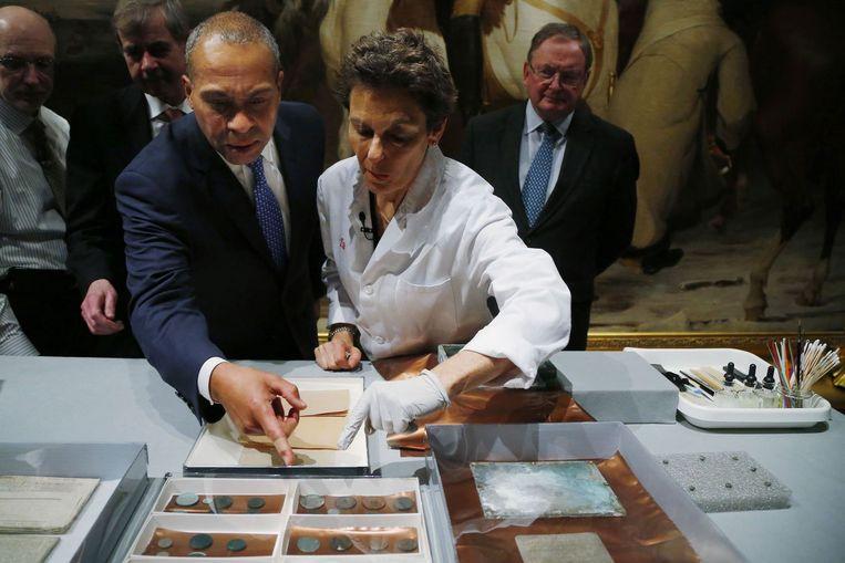 Gouverneur Deval Patrick van Massachusetts en museumconservator Pam Hatchfield bekijken de voorwerpen uit de doos. Beeld reuters