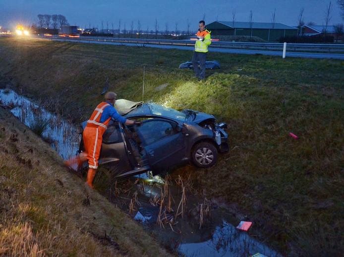 Hulpverleners zijn in de weer met de van de weg geraakte auto.