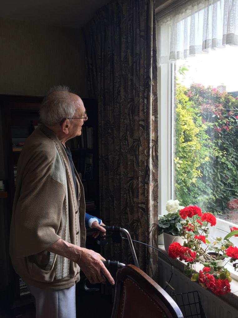 Frits geniet van zijn favoriete uitzicht: 'Kijk, de rozen bloeien nog steeds'.  Beeld Desiree van den Bogaard