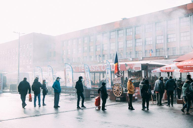 Roemenen wachten voor een kraampje op de Obor-markt. Beeld Marlena Waldthausen