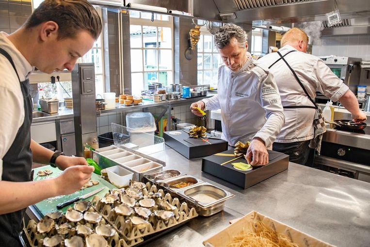 Chefkok Wilco Berends helpt mee met het klaarmaken van doosjes oesters die klanten online hebben besteld. Zijn restaurant De Nederlanden probeert op deze manier de omzet enigszins te behouden. Beeld Guus Dubbelman / de Volkskrant