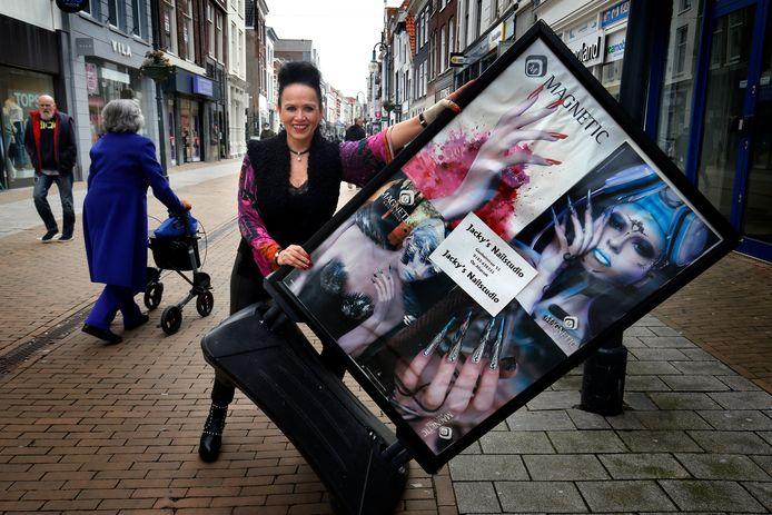 Jacky Bakhuys met het reclamebord voor haar nagelstudio dat ze eerder deze week onmiddellijk binnen moest halen van gemeentelijke toezichthouders.
