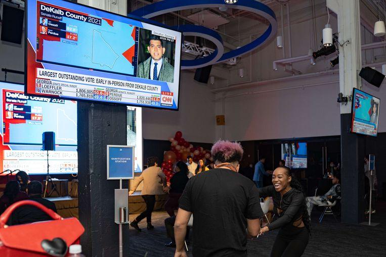 Dansende inwoners van Atlanta als de peilingen woensdag duiden op een gunstig verkiezingsresultaat voor de Democratische kandidaten uit Georgia voor de Senaat.  Beeld AFP