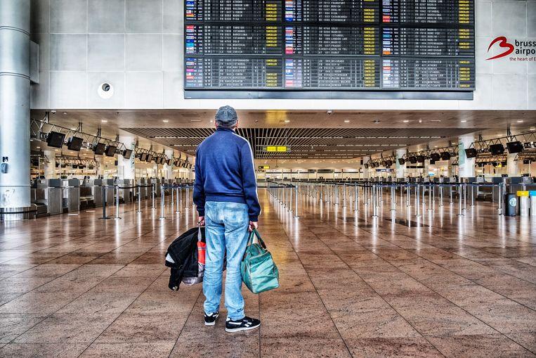 Een assagier bekijkt het bord met geannuleerde vluchten op Brussels Airport.  Beeld Tim Dirven