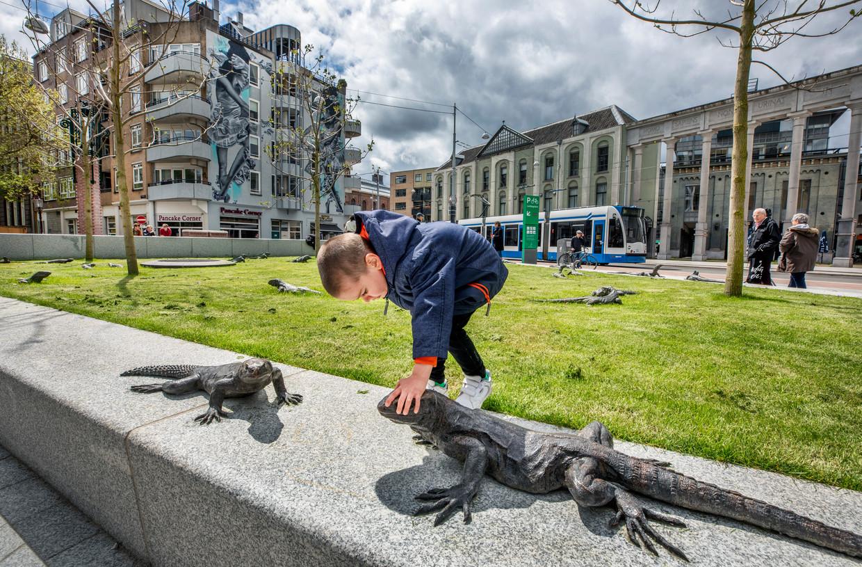 Het Leidseplein in Amsterdam is 28 mei officieel heropend. Onder het grasveld is een grote fietsenstalling. De leguanen en hagedissen van kunstenaar Hans van Houwelingen, ook nu weer bij het ontwerp betrokken, zijn gebleven.  Beeld Raymond Rutting / de Volkskrant