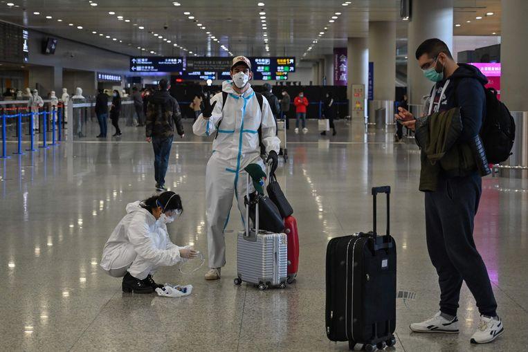 Passagiers met beschermende pakken op de internationale luchthaven van Shanghai.