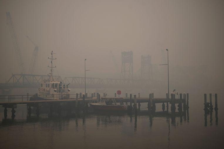 Smog van de branden hangt over de haven in Batemans Bay. Beeld AFP