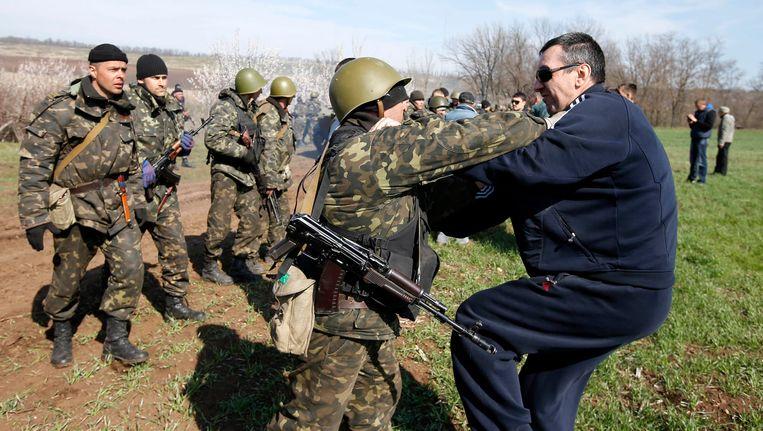Een Oekraïense soldaat krijgt het aan de stok met een pro-Russische demonstrant in een veld in het oosten van Oekraïne. Beeld REUTERS