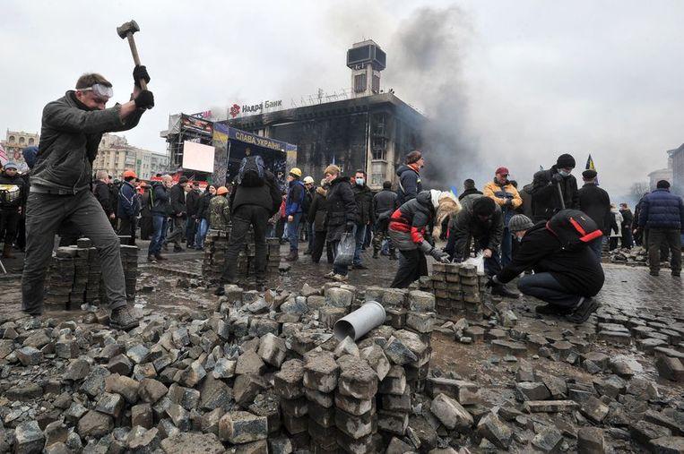 Demonstranten halen stenen uit de straat om deze te gooien op de politie. Beeld afp