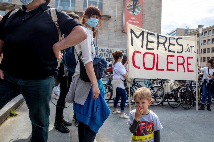 """Les femmes du collectif portaient des t-shirts blancs. Des fleurs blanches parsemaient la foule. De grandes banderoles blanches arboraient les messages """"Mères en colère"""" et """"Stop aux violences policières sur nos enfants""""."""