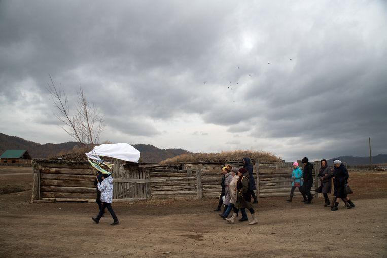 Dorpelingen halen de bruid op voor een traditionele sjamanistische huwelijksceremonie, Altaj, West-Siberië. Beeld Claudia Heinermann
