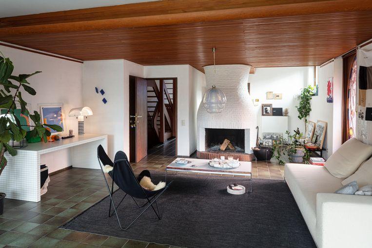 Het verlaagde houten plafond verdeelt de woonkamer optisch in tweeën.De imposante bakstenen  schouw is het opvallendste element in de zithoek en de reden waarom het gezin geen tv in de living heeft. Beeld Tim Van de Velde