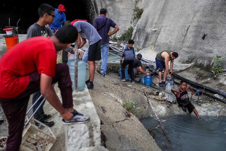 Inwoners van Caracas halen water bij een verlaten gebouw. Beeld EPA
