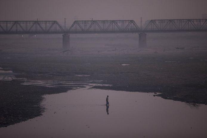 Een man staat in een half opgedroogde rivier met smog om hem heen in Agra in de Indiase staat Uttar Pradesh. De foto werd begin 2019 genomen.