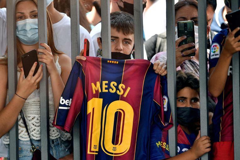 Aan het hek rond Camp Nou proberen fans een laatste glimp van hun idool Lionel Messi op te vangen, voor hij naar Parijs vertrekt. Beeld AFP