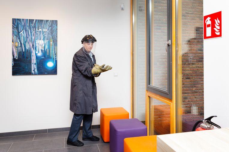 'Bankside Birches 2' van Hans Vandekerckhove aan de muur van de 'invoerruimte' van het crematorium in Leiden. Rechts een ovenist, een medewerker die de oven bedient.  Beeld Pauline Niks