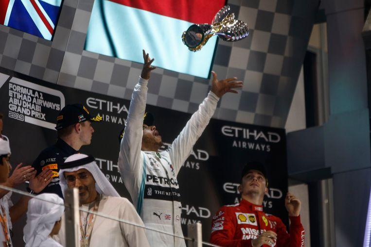 Hamilton gooit zijn trofee in de lucht op het podium in Abu Dhabi. Beeld Photo News