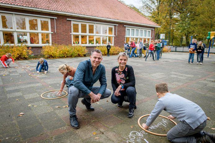 Voorzitter Mark Oude Luttikhuis van Dynamiek Stokkum en schoolhoofd Dorien Klein Teeselink. Leerlingen vullen de oplossing van een rekensom in hoepels op het schoolplein in.