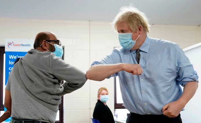 De Britse premier Boris Johnson geeft een elleboog aan een man die net een vaccinatie heeft gekregen.