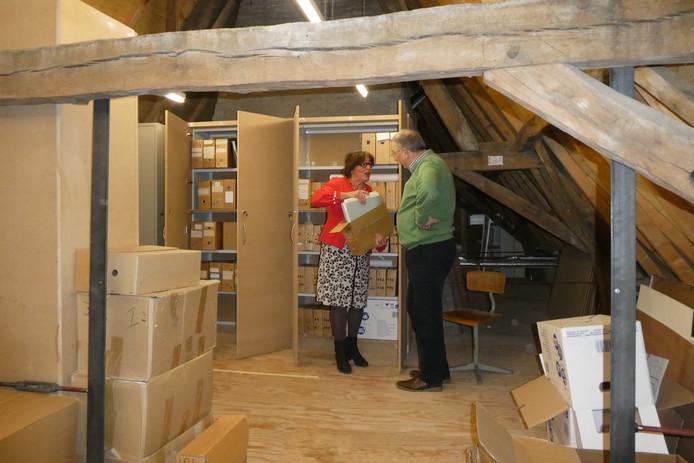 Op zolder zijn nieuwe archiefkasten gebouwd bij 't Hofje voor de Heemkunde Boxtel. Hanneke van der Eerden en Christ van Eekelen bergen spullen op.