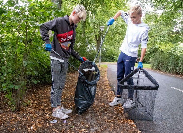 """Sam Versluis (rechts) en Sasha Boone rapen afval op langs het Bolwerk en uit de vest in Middelburg. ,,We doen iets voor het milieu en het betaalt goed"""", verklaren de vrienden."""