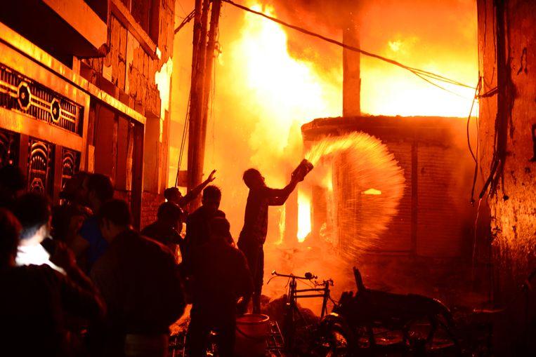 Brandweermannen en vrijwilligers proberen in Dhaka het vuur te bedwingen. Beeld AP
