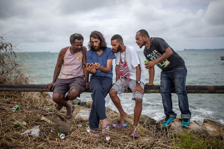 Behrouz Boochani laat inwoners van Papoea-Nieuw-Guinea foto's zien van zijn geboortestad Ilam, in Iraans Koerdistan.  Beeld LightRocket via Getty Images