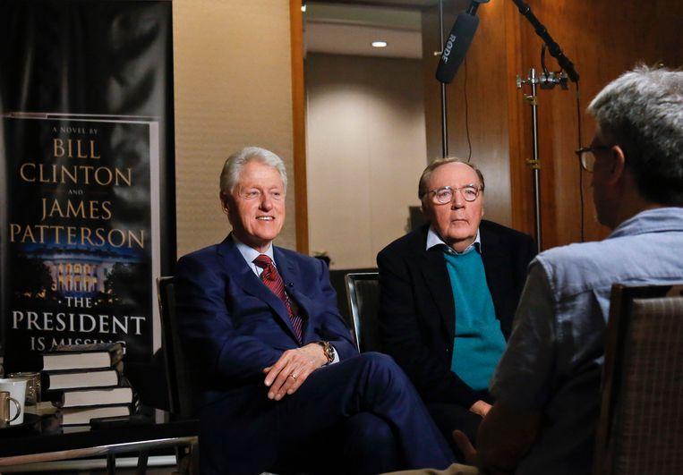 Bill Clinton en auteur James Patterson in 2018, bij de release van hun boek 'The President is Missing'. Beeld AP