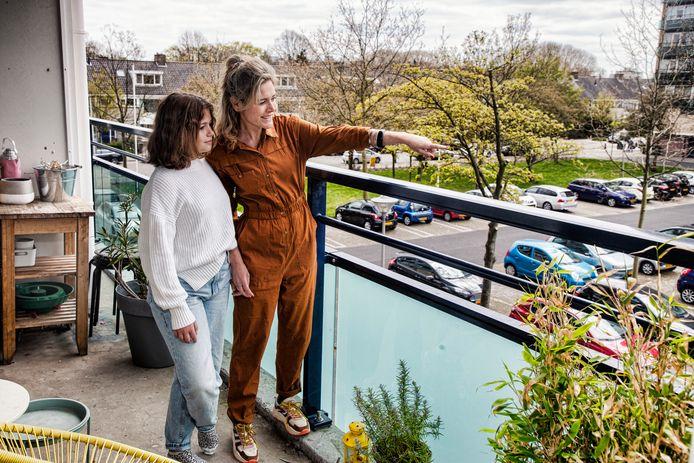 Maike Thornissen (r) met haar dochter op het balkon van haar huurflat in Tuindorp. Ze wil graag kopen maar kan dat in haar situatie niet.