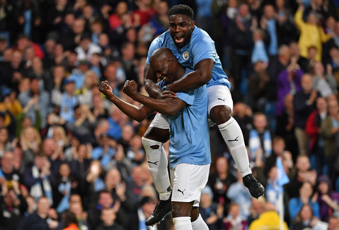 Benjani (l) heeft vlak voor tijd de 2-2 gemaakt namens de Manchester City-legends. Hij viert de treffer met Micah Richards.