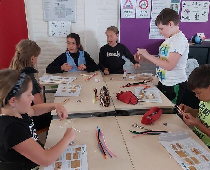 Kinderen van de Maria School in Bladel maken een 'Blink Bug' van ASML gekregen in het kader van de Dutch Technology Week.