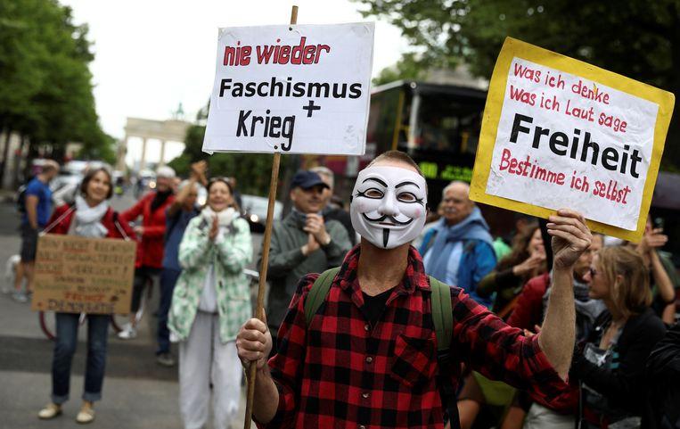 Een demonstrant in Berlijn draagt een masker en een bord met de teksten