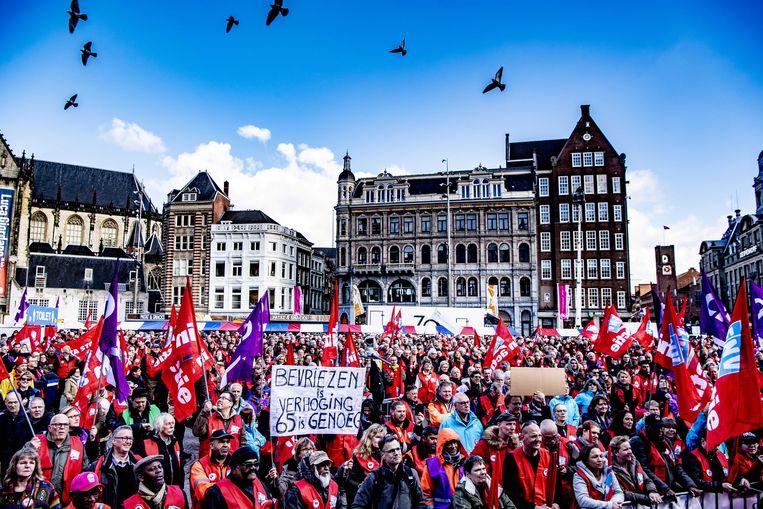 Stakers demonstreren op de Dam tijdens de landelijke actiedag voor een goed pensioen. Vakbonden eisen dat de AOW-leeftijd wordt bevroren op 66 jaar. Beeld ANP, Robin Utrecht
