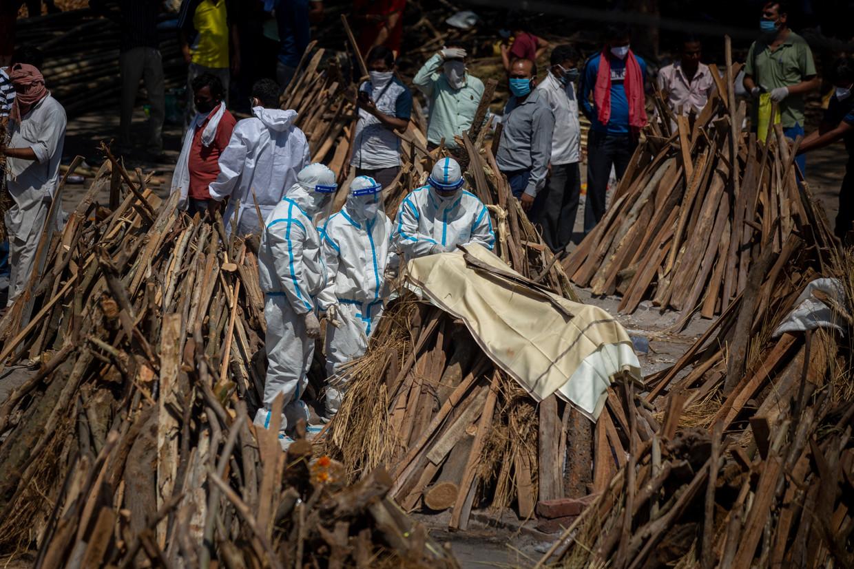 Slachtoffers van het coronavirus worden gecremeerd in de Indiase hoofdstad New Delhi. Begraafplaatsen en crematoria kunnen het aantal doden amper aan. Beeld AP