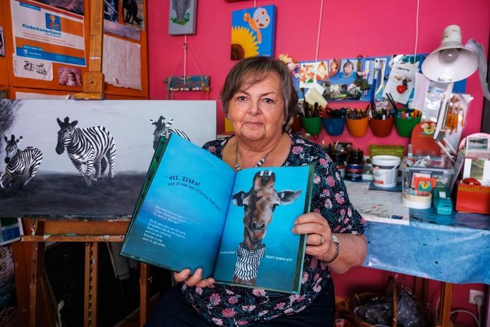 Rit Dierckx, schilderes en ex-kleuterleidster, toont de illustraties van haar boek.