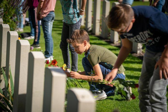 Kinderen leggen bloemen op de  Airborne begraafplaats in Oosterbeek.