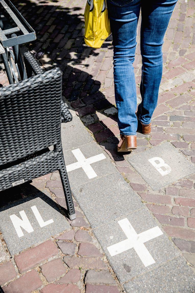 De grens met België loopt vlak naast de laatste terrasstoel van brasserie Den Engel.  Beeld Aurélie Geurts