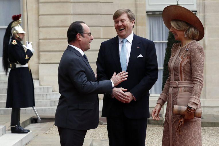 Hollande maakt een grapje tijdens het ontvangst van Willem-Alexander en Máxima. Beeld reuters