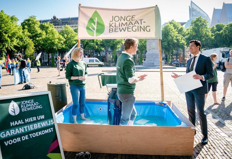 Actie van de Jonge Klimaatbeweging voor de Tweede Kamer. Een bak water symboliseert de dreigende stijging van de waterspiegel.  Beeld ANP
