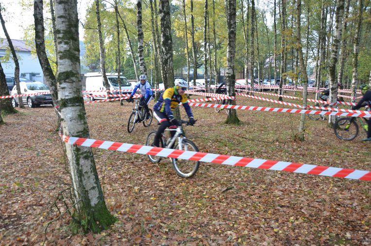 De mountainbikers slalommen tussen de bomen van het Bospark.