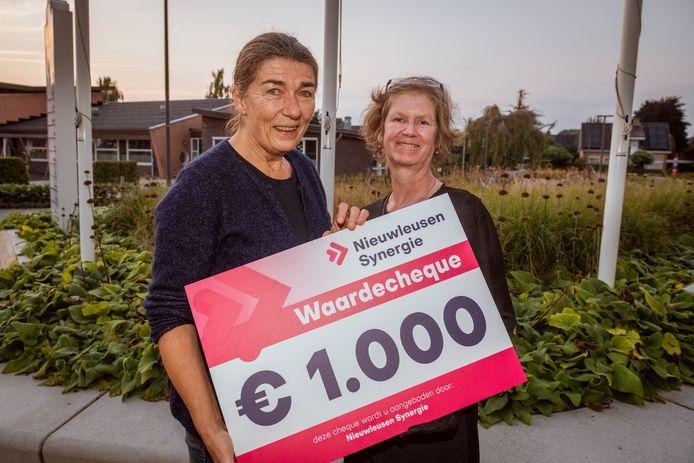 Ineke van den Berg (l) en Ali Bloemert en van Belangenvereniging Nieuwleusen Buitengebied West hebben een van de cheques van duizend euro gekregen van Nieuwleusen Synergie.